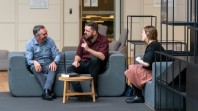 three seated people chatting