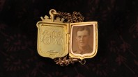 A gold locket showing a photo of Eric Chinner on the right and his initials on the left