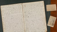 An old handwritten diary lays open beside photos of a US Confederate soldier and a clipper ship