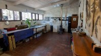 interior shot of printing studio with tiled floor, wooden roof, potbelly stove, sinks, drawers and equipment