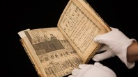 Photo of a book containing a notice about King Charles' execution being held by a person wearing white gloves