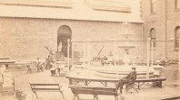 faded photo of men seated in exhibition courtyard