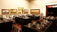 Photo of tables set up in Cowen gallery with black tablecloths and cutlery