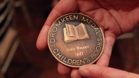 round metal medal held in hands inscribed with the words 'Dromkeen Medal. Children's books. Erica Wagner 2017'