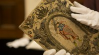 Colour photo of gloved hands holding colourfully embroidered historic binding thought to belong to Queen Henrietta Maria, wife of King Charles I, c1630