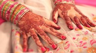 woman's hands covered in henna art with bangles, embroidery and red nail polish