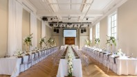 Three rows of long tables covered in white tablecloths and strewn with flowers