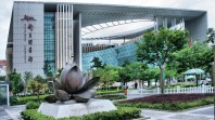 Modern Chinese building with lotus sculpture, curved glass walls, trees and gardens