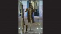 glass display case with Ned Kelly helmet, armour, rifle and boot