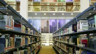 colour photo of library interior with books of shelves and glassed-in mezzanine