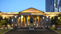 Colour photo of facade featuring spotlit classical portico and columns against blue sky at dusk