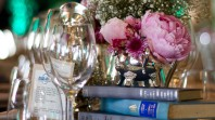 Photo of flowers and books set up on a table for a special event