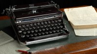A manual typewriter sits beside typed pages on a leather-padded desk