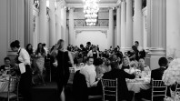 Black and white photo of dining event set against the columns and chandeliers of Queen's Hall