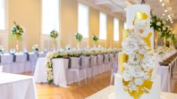 elegant wedding venue with formal tables, cake and sunlit windows