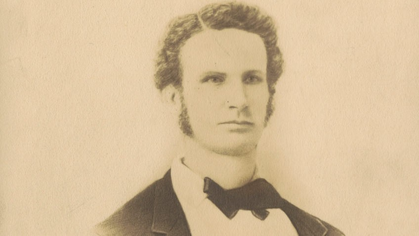 sepia photo of curly-haired man wearing bow tie