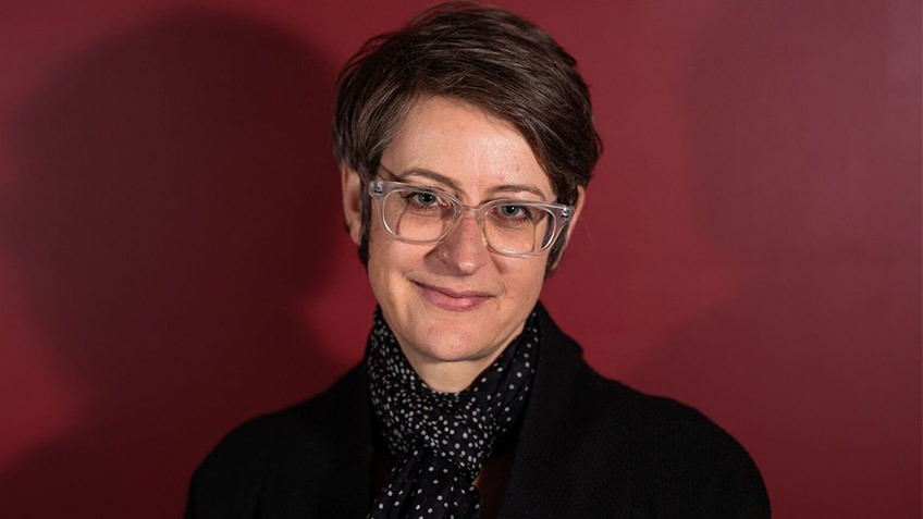 portait of woman with short hair and clear spectacles against red background