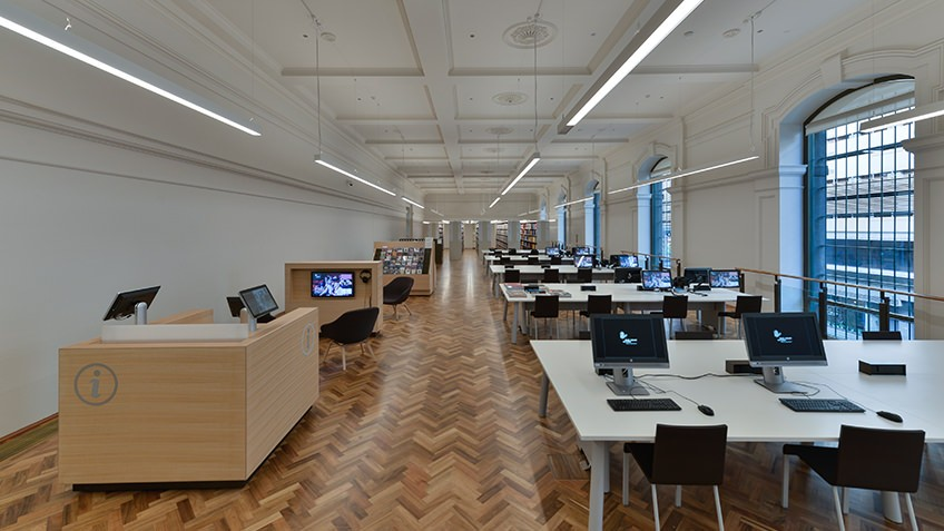 desks and tables in parquet-floored white gallery