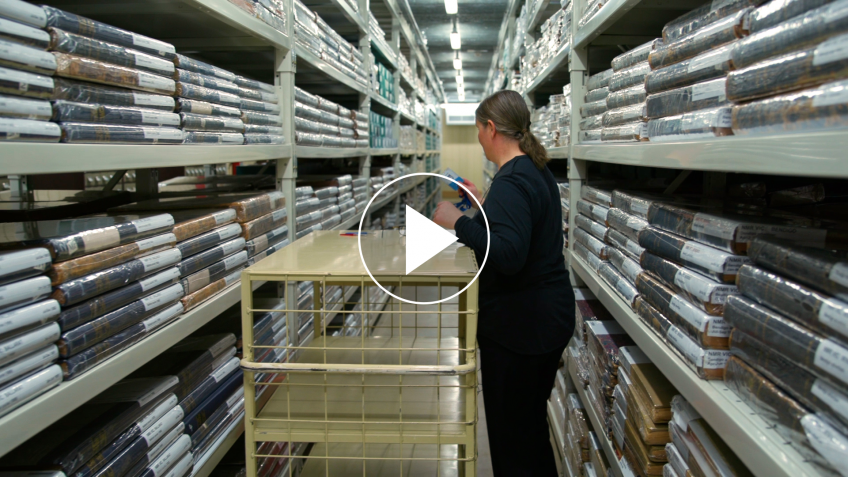 Woman standing amongst shelves of books