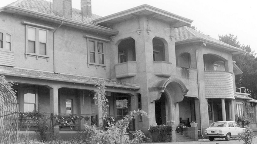 B&W photo of 1920s mansion with turrets and arches