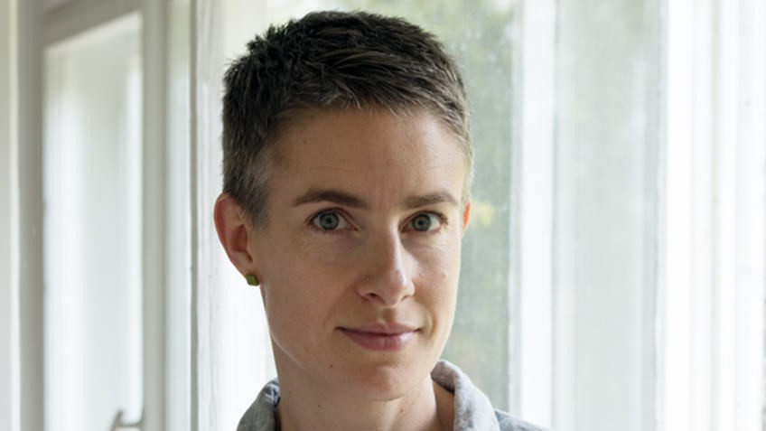 woman with short grey hair photographed backlit against white curtains