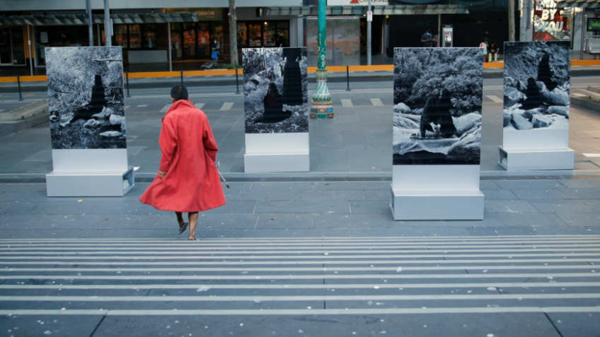 Grey city scene with a person walking in a red coat