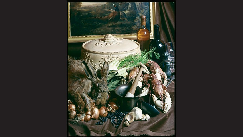 Decadent tableau of raw ingredients for a casserole arranged on a table in front of a landscape painting