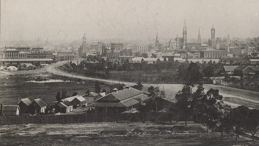 Melbourne viewed from south side of the Yarra river, showing St Kilda Road, site of Princes Bridge, fish market, Town Hall, spires of Scots Church and Independent Church. In foreground: Immigrants Aid Society Depot on left, Immigrants Home on right.