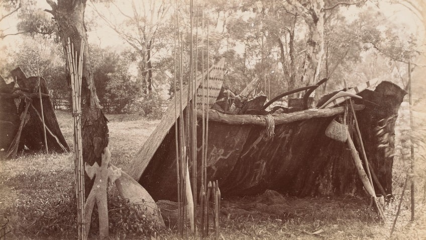 sepia photo of bark lean-to with Aboriginal tools, art and baskets