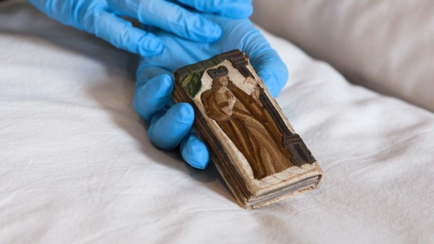 Gloved hands holding a small book