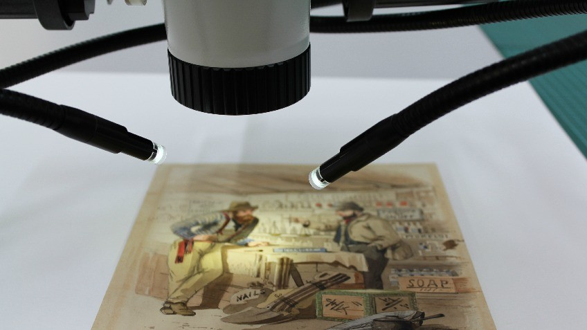 Image of a microscope positioned over an artwork