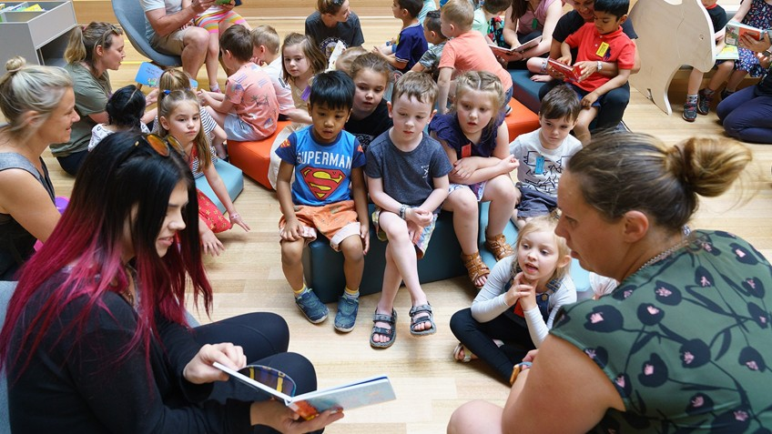 two women presenting a book reading to seated children