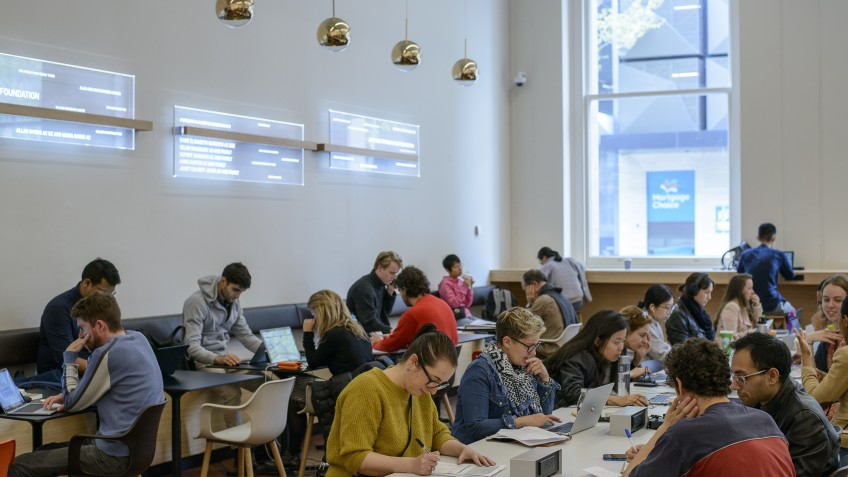 people studying at long tables in a bright room