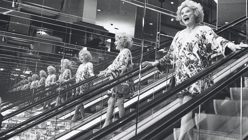 black and white photo of smiling woman on escalator reflected in mirrors