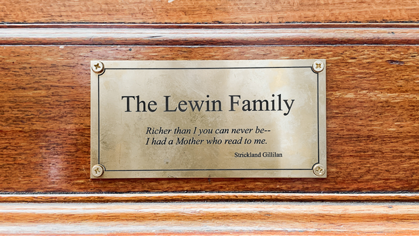 An inscribed bronze plaque on a wooden background