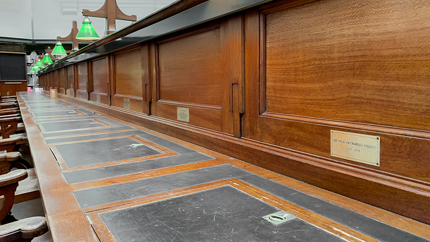 A row of desks with bronze plaques inscribed into them