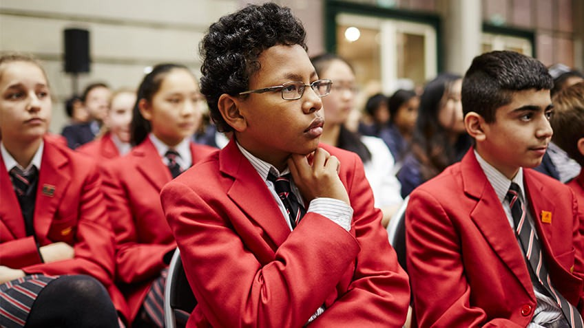 Colour photo of an audience of schoolchildren wearing red blazers
