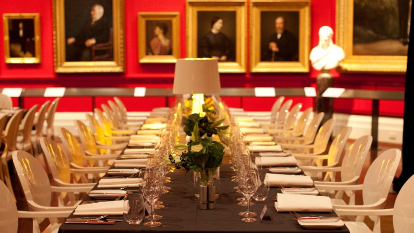 Colour photo of formal table setting for large dinner party in red-walled Red Rotunda with portraits