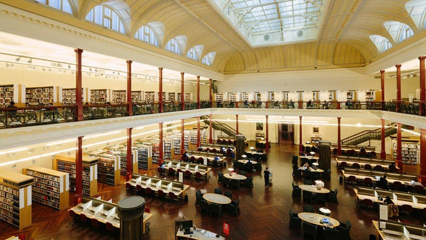 heritage reading room with mezzanine balconies, glass roof, shelves of books and study tables