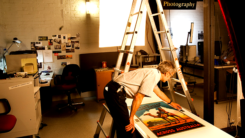 A man leans over a poster on a table with a large light and ladder nearby