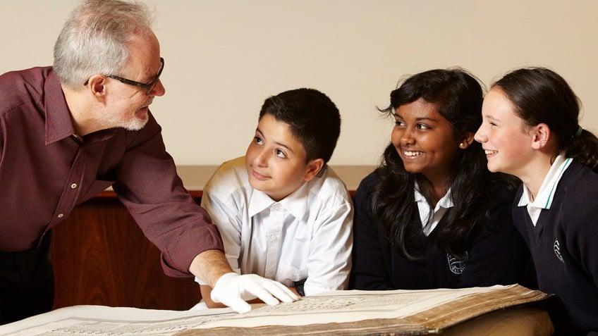 A man teaching three children