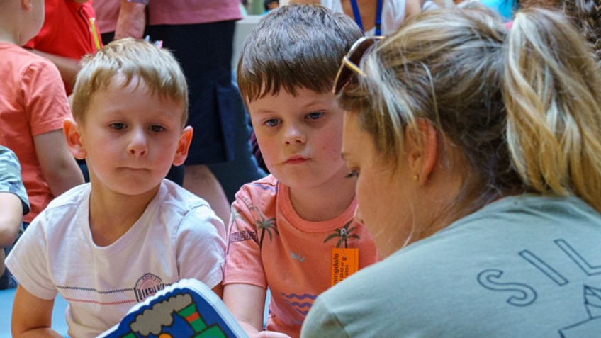 Two children being read a book