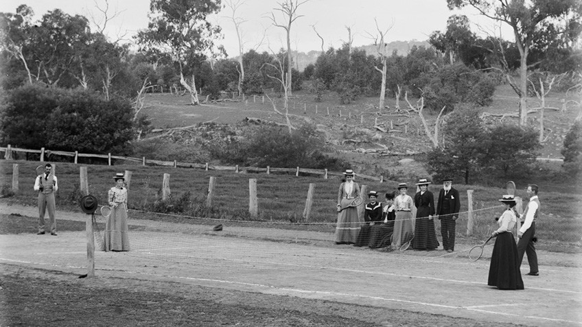Men and women in straw hats, trousers and long skirts play tennis in bush surrounds