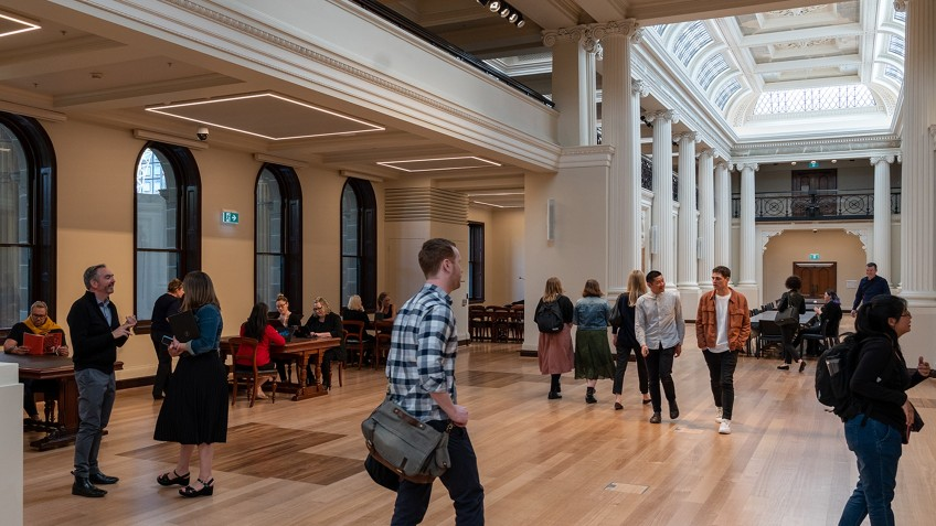people in public space with pillars and coffered ceiling