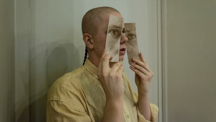 person holding bookmarks up to cover their eyes
