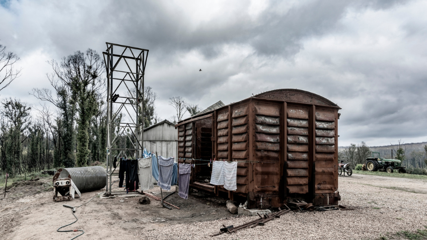 A burnt out train carriage with grey skies behind it