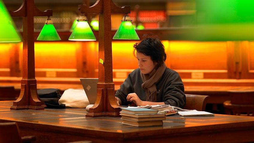 A high school student writes beneath a green desk light in a dim room
