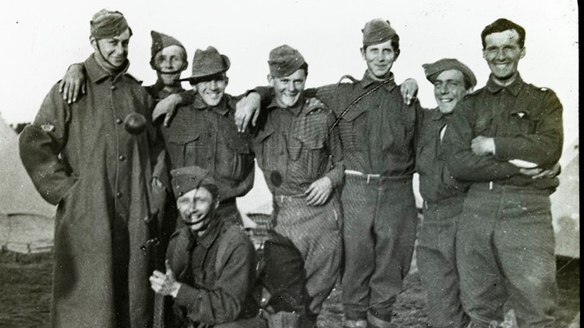 B&W photo of WWI soldiers wearing military uniforms, looking cheerful