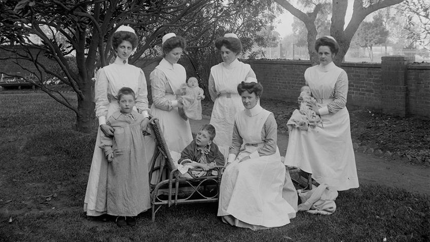 black and white photo from 1890 of nurses holding infants