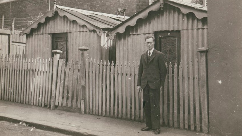 Corrugated-iron hut housing in North Melbourne photographed in the 1930s pictured with slum-clearance advocate FO Barnett